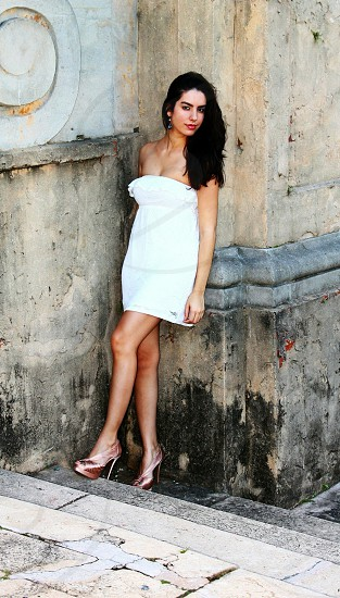 woman wearing white strapless short dress and metallic heels on steps photo