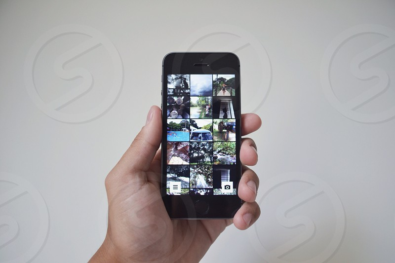person holding a black iphone 5 photo