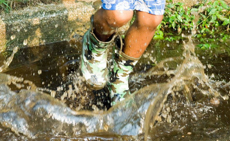 person wearing camouflage boots jumping on water photo
