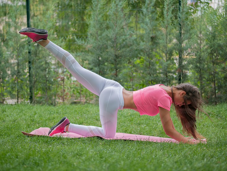 Beautiful sexy young caucasian woman in fitness wear working out in a park. Lady with long hair and outfit doing sport exercises on the athletic mat. photo