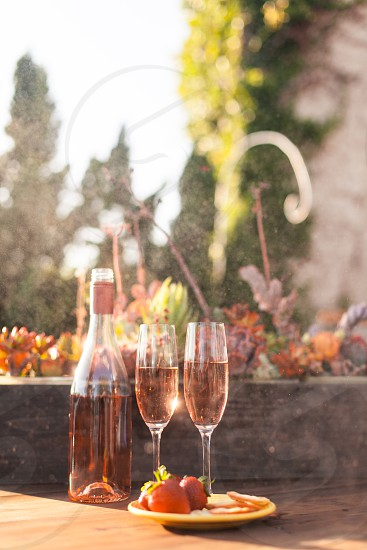 two champagne flutes filled with rose wine on a table next to a bottle and a plate of strawberries and crackers photo