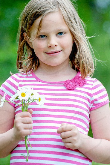 girl with white and purple striped dress holding a white and yellow flower photo