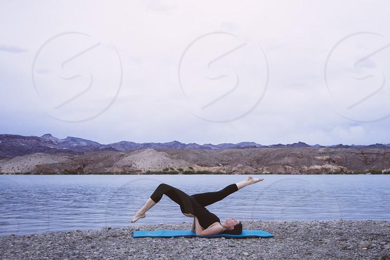 woman doing yoga beside the lake photo