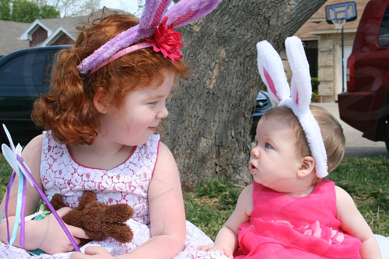 Really cute big sister and and adorable baby sister looking at each other and wearing bunny ears on Easter. photo