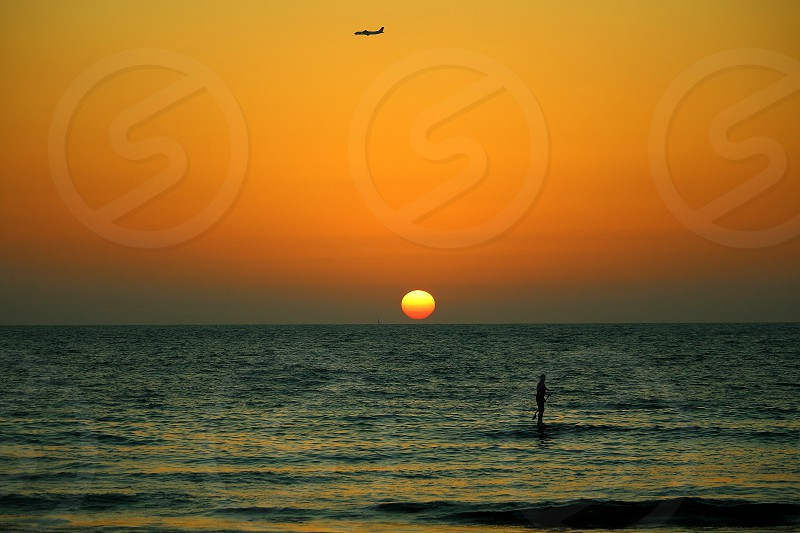 surfing in the sea with a plane flying over the sun at sunset photo