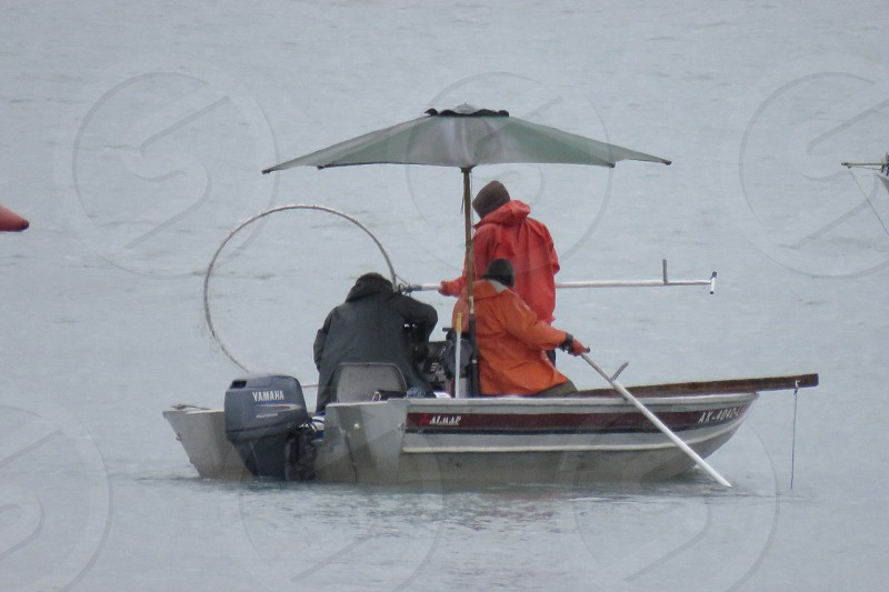 Fishing boat dip netting with two people onboard during a dreary day photo