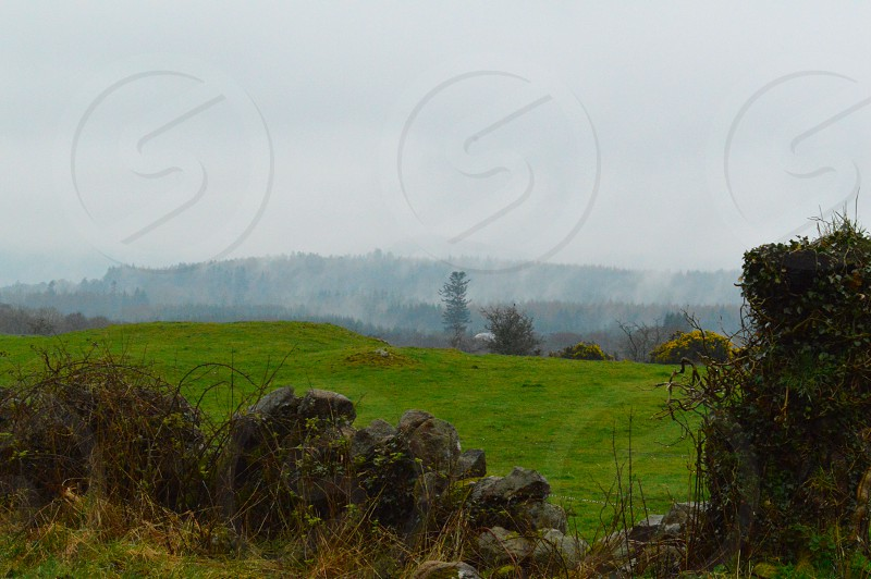 Mist rolling into the trees on some distant hills near Sweetheart Abbey in Dumfries Scotland on a cloudy day. photo