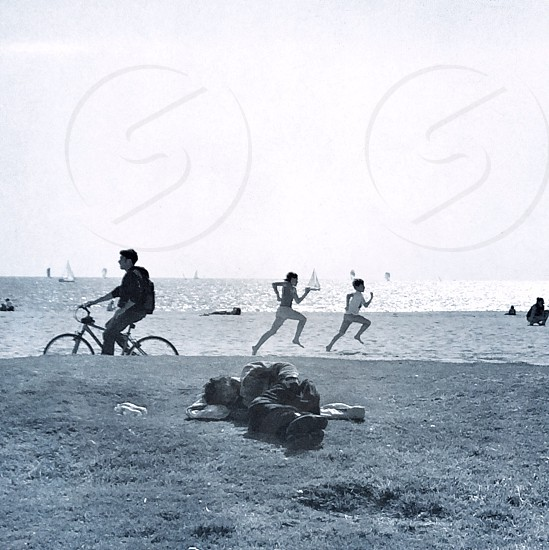 gray scale photo of person lying on grass man riding in bike and two women running on seashore photo