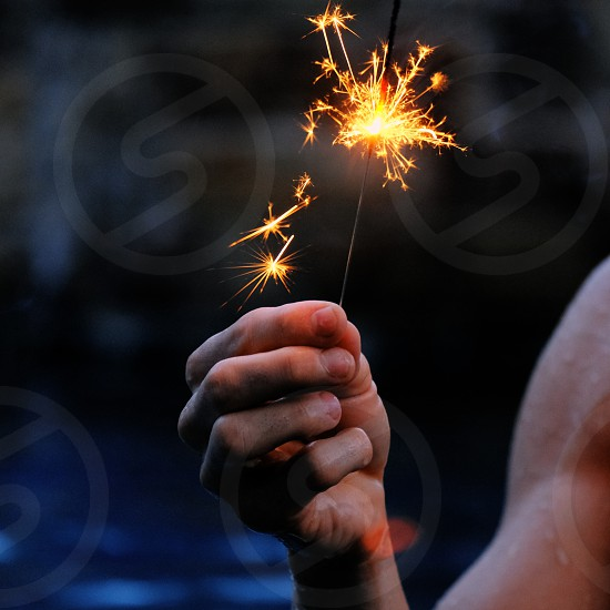Person holding sparkler during dusk for 4th of July. photo