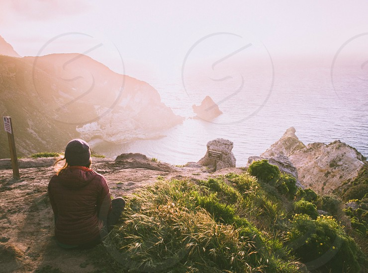woman wearing red hoodie sitting on top of the mountain overlooking the ocean with sun rays during daytime photo