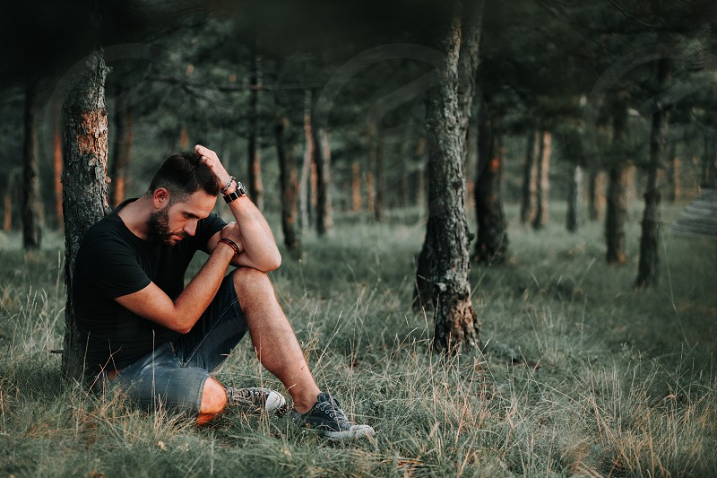 Young depressed man sitting alone in the forest photo