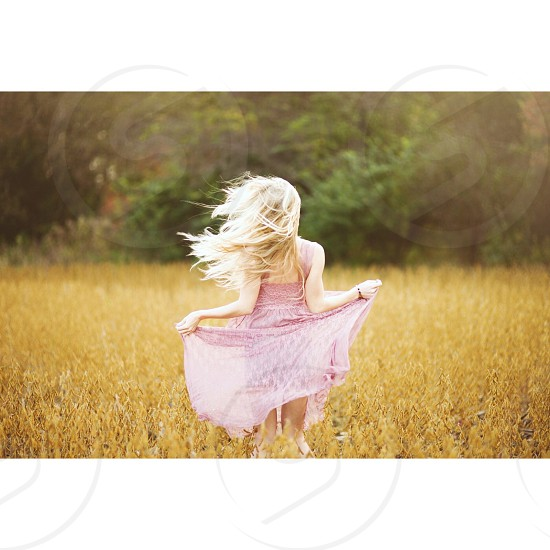 woman lifting pink dress on waist while standing on brown grass field during daytime photo