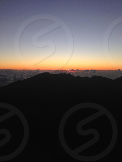Sunrise above the clouds on the volcano peak photo