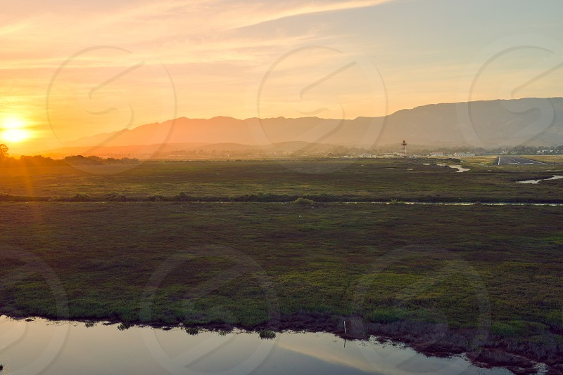 sunset airport mountains goleta reflection clouds sky sun flare green photo