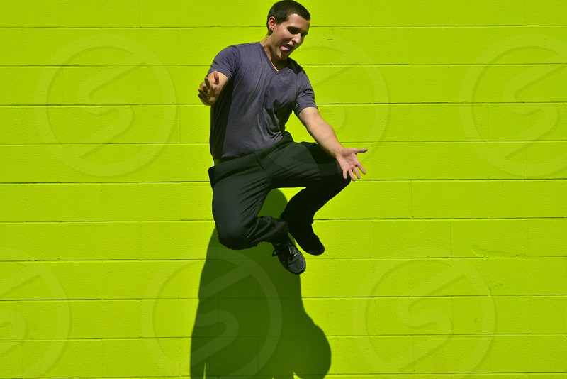 man in grey v neck t shirt and black pants jumping in front of a green concrete wall photo