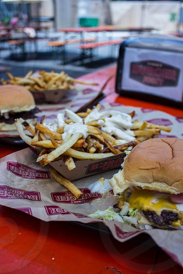 potato fries with white cream beside 2 cheese burgers from burger joint placed on white table photo