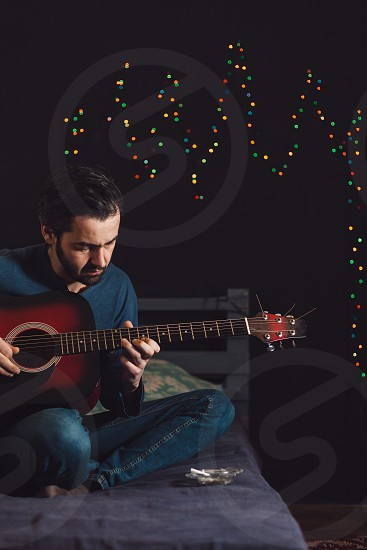 Young man playing guitar and composing a song photo
