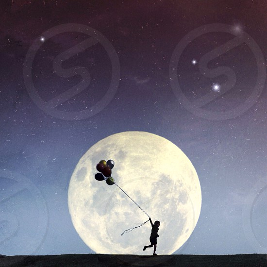child running with balloons past a giant full moon photo