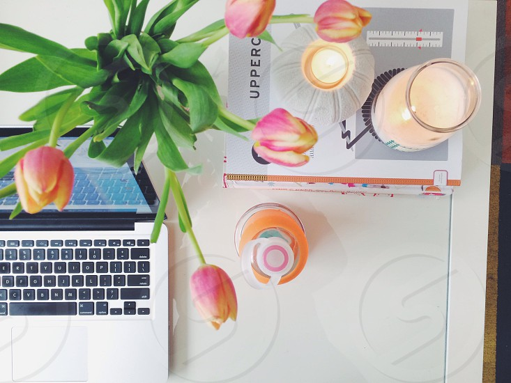 MacBook Pro tulips and a stack of magazines under a tea light with an orange water bottle.  A bright white workspace home office for a designer.  photo