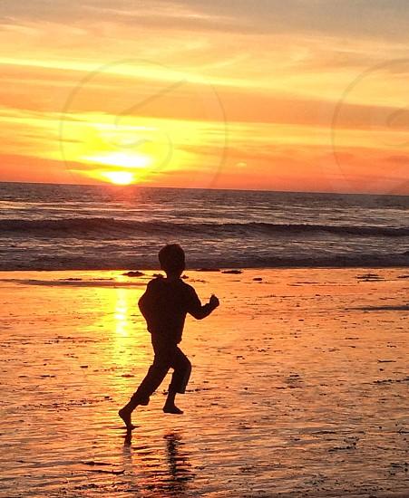 Running into the sunset . Hendry's beach Santa Barbara  ca photo