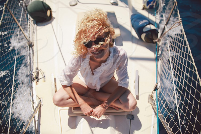 Santorini Greece boat trip travel vacation girl smiling curly hair hair in the wind sunglasses white shirt sea sunny photo