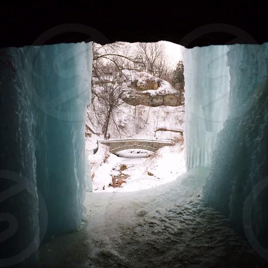 ice glacier walls overlooking snowy river and bridge way photo