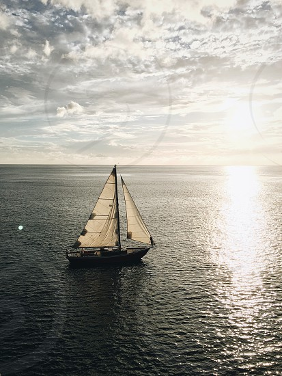 white and brown sailboat on water photo