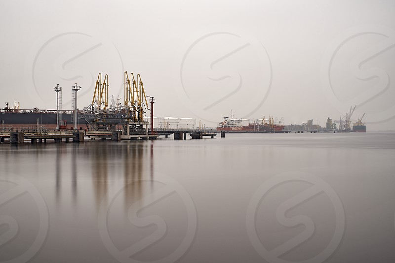 A containership being loaded or unloaded at the port of Amsterdam on a misty cloudy day in autumn photo