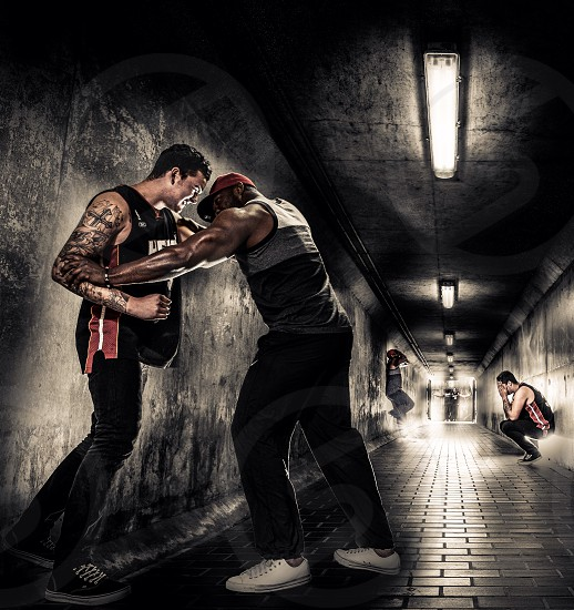 A tattooed white man wrestling a black muscle man in a tunnel one with them reappearing further down in the poses of regret and final reconciliation at the end of the tunnel photo