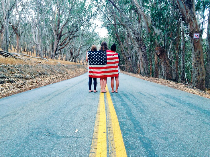 3 women holding us flag standing on the road photo