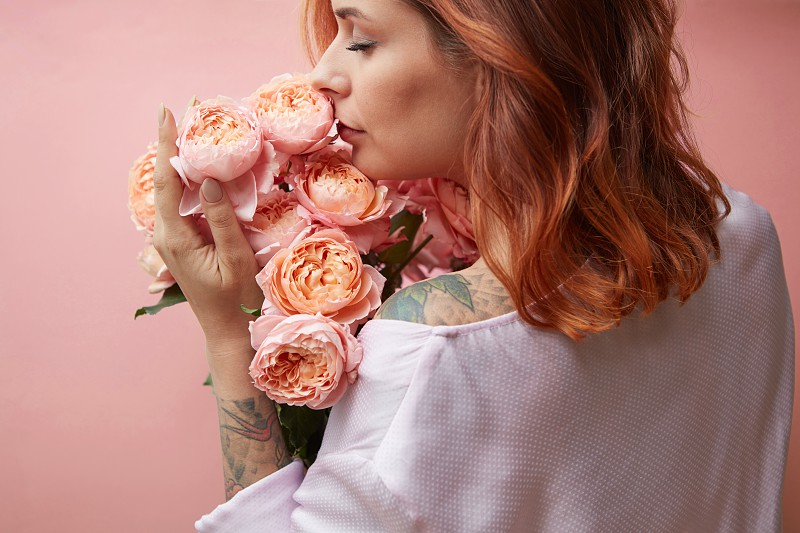 Beautiful girl with fragrant flowers on a background in a trendy color of the year 2019 Living Coral Pantone. Mother's Day and Valentine's Day greeting post cards. photo