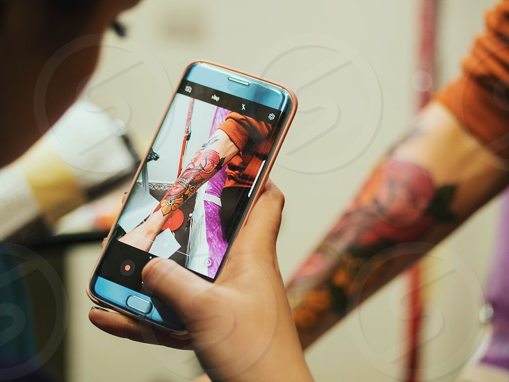 Young female tattooist artist making photo on her smartphone of tattoo on man's arm of client. Using technology. photo