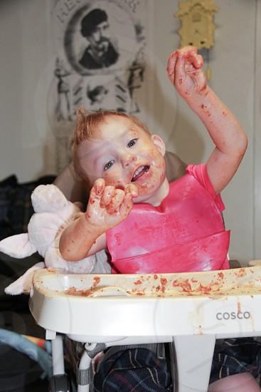 baby wearing red bib on white cosco high chair photo