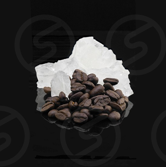 crystal sugar and coffee beans  over black reflective surface background photo