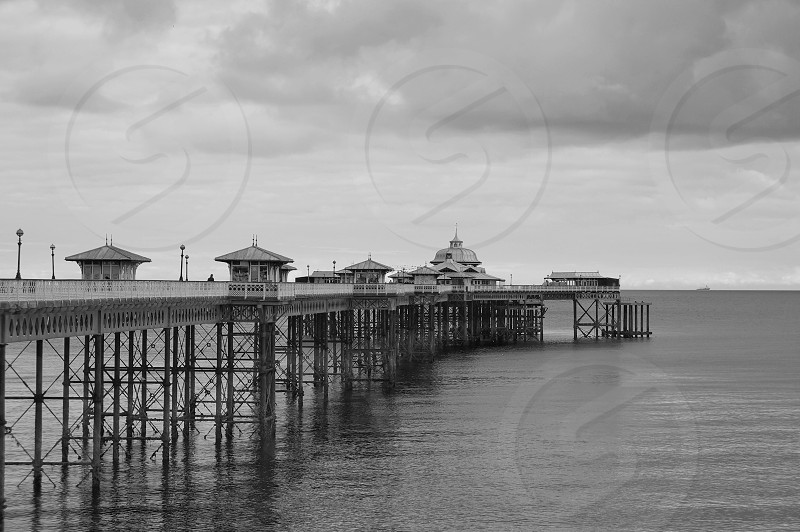 Black and white shot of a pier and buildings stretching out into the ocean photo