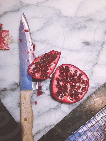 slice pomegranate beside a brown handled knife photo