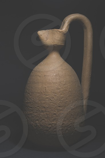 beige stone pitcher in the dark photo