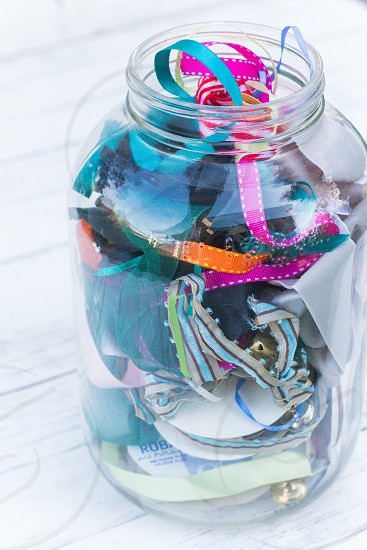 A large glass jar full of different coloured ribbons photo
