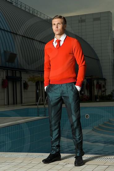 man in orange sweater and black khaki pants near swimming pool during daytime photo