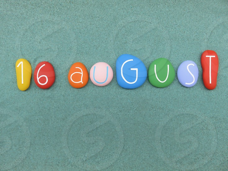 16 August calendar date composed with multi colored stones over green sand             photo