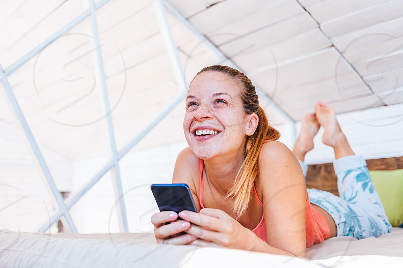Young woman using cellphone at home happy connection photo