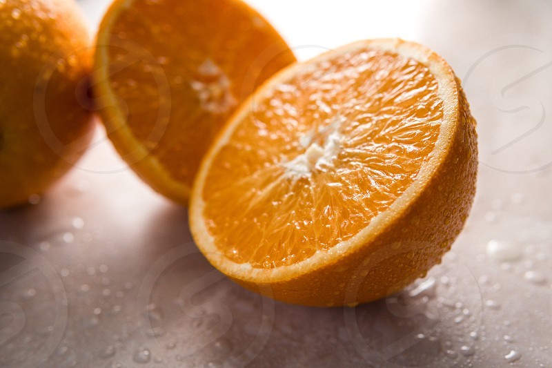 Orange covered with rain drops on the marble background photo