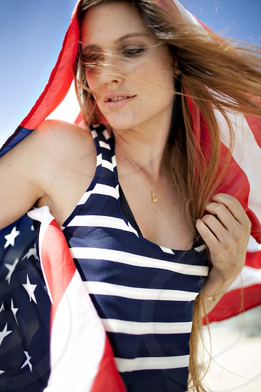 woman in white and black stripe tank tap with usa flag on head photo