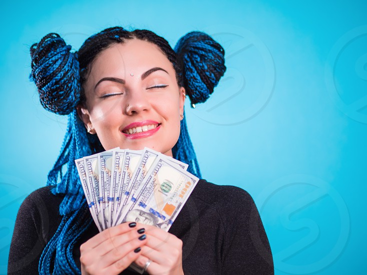 Happy smiling woman holding cash money dollars and thinking how to spent its. Toned portrait. Hipster girl with blue dyed braids african hairstyle in studio. photo