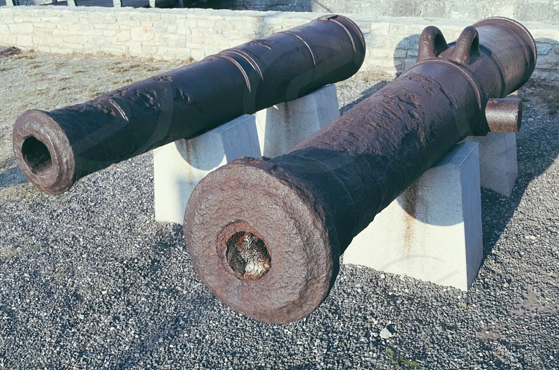 Two Old Rusty Naval Artillery Cannons on White Stone Pedestal photo