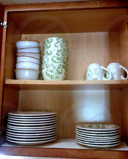 Cabinet full of dishes bowls cups saucers and plates photo