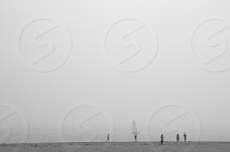 Black and white image of tiny people seen in the distance on a foggy beach photo