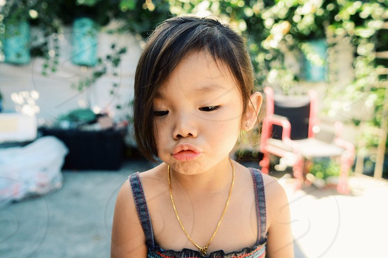 girl in gold necklace and tank dress making pucker face photo