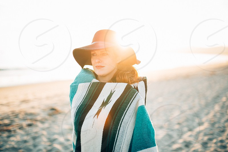 woman in black wide brimmed hat covered with black blue blanket walking at the beach photo