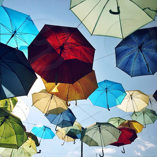 colored umbrellas hanging on a wire  photo
